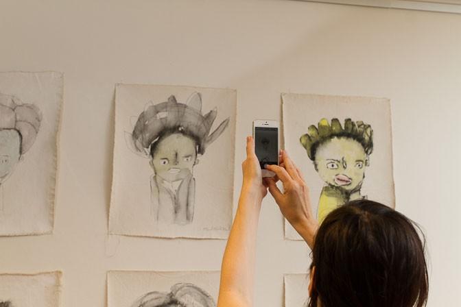 Portraits von Baby Appachan sehen sich bei der Vernissage fotografiert.