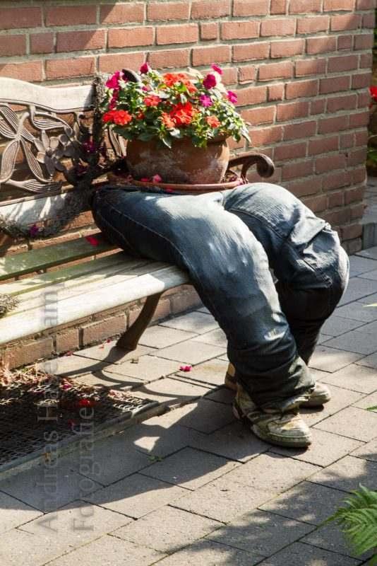 Blumentopf in Hose auf einer Sitzbank eines Hauses in Angelmodde-West.