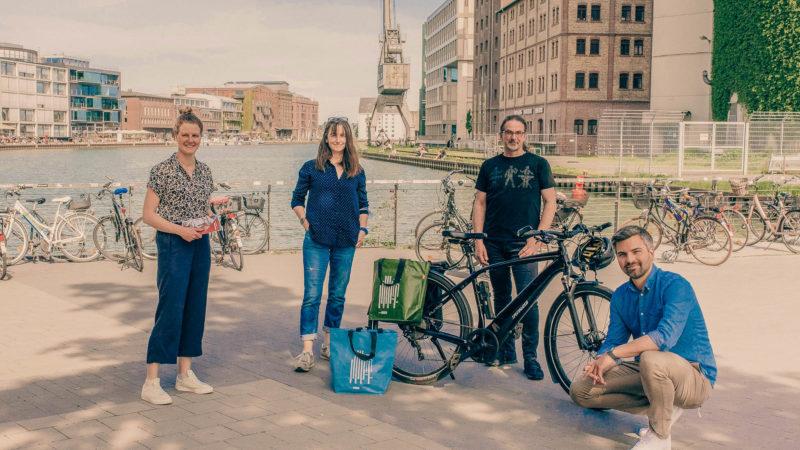 Annika Schröder vom Fahrradbüro der Stadt Münster bedankte sich bei den Gewinnerinnen und Gewinnern für die Teilnahme an der Aktion. Annette Nettebrock, Martin Neiss und Peter Bodenbenner freuen sich über die Gutscheine.Foto: Stadt Münster.