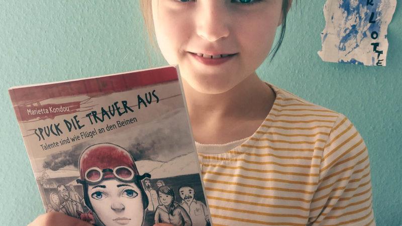 """Die zehnjährige Charlotte gab die Anregung, das Kinder- und Jugendbuch """"Spuck die Trauer aus"""" auch auf Deutsch lesen zu können. Nun hält sie ein druckfrisches Exemplar der übersetzten Ausgabe in den Händen. Foto: Privat."""