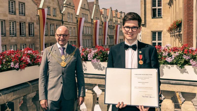 Dennis Hartjes (links) erhält Bundesverdienstmedaille von Oberbürgermeister Markus Lewe. Foto: Amt für Kommunikation, Stadt Münster.