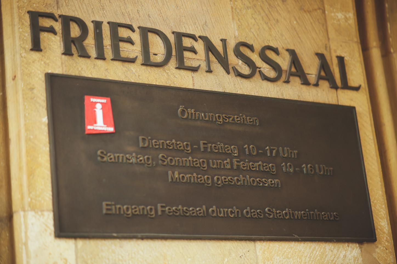 """Bronze-Schild """"Friedenssaal"""" neben dem Eingang zum Friedenssaal im historischen Rathaus zu Münster. Foto: A. Hasenkamp."""