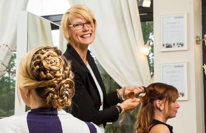 Christiane Wegner nimmt die Haare von Lia Freudenberg zum Flechten in den Griff – bei Saskia Walterbusch ist das vollendete Werk zu sehen. Foto: Andreas Hasenkamp.