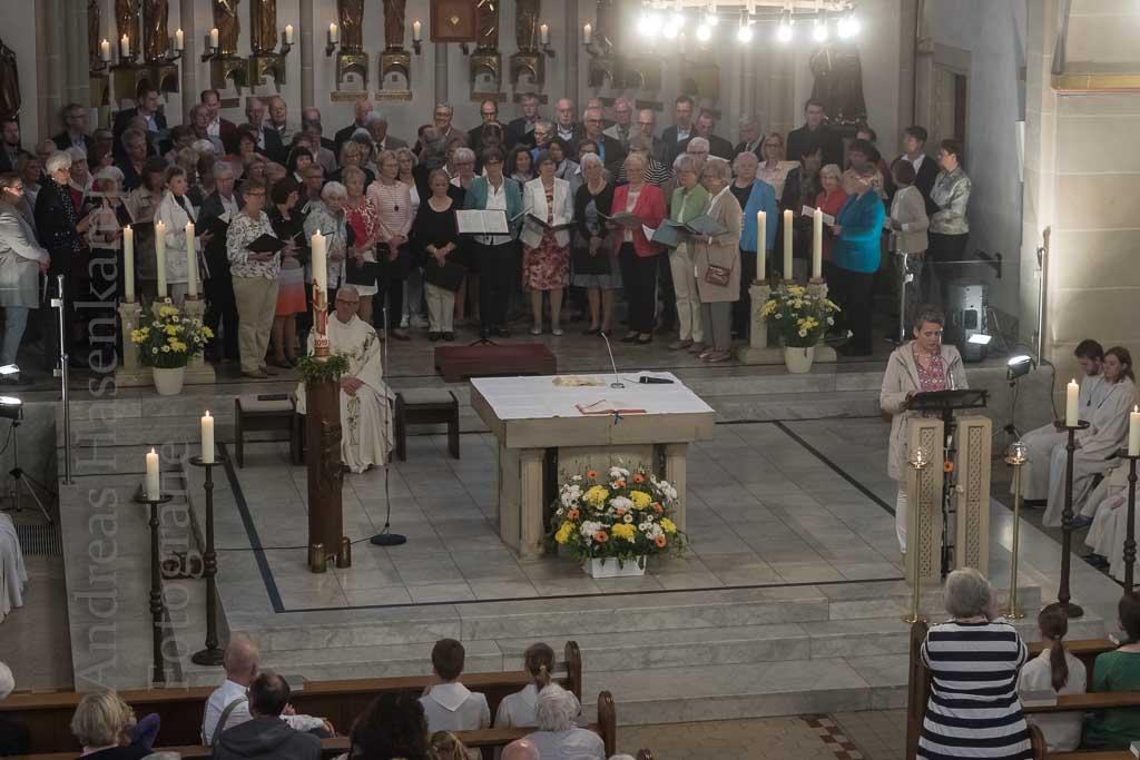 Chöre und Pfarrer Mike Netzler hinter dem Altar, Frau am Ambo