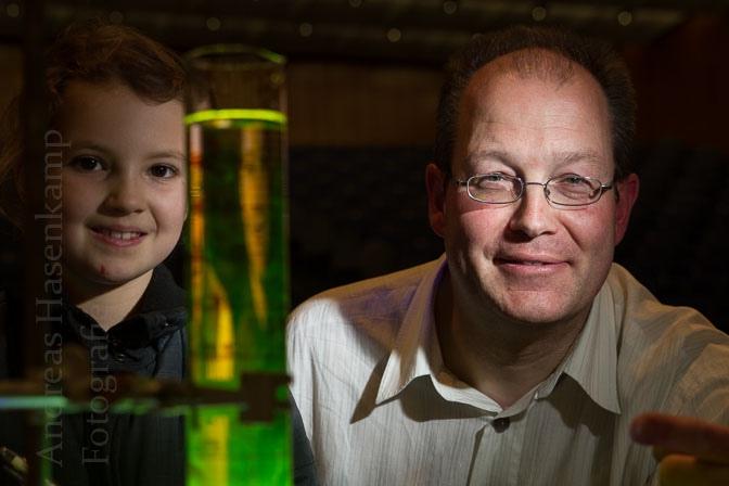 Ein paar Krümel Fluorescin in das große Reagenz-Glas mit Wasser - schon erzeugt Chemie Leuchten: aus der Nähe schauen zu Kinder-Reporterin Eva Babel und Professor Uwe Karst. Foto: A. Hasenkamp, Fotograf in Münster.