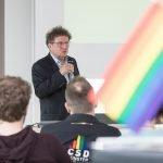 Sprecher mit Regenbogen-Flagge und CSD-Aufschrift auf T-Shirt.