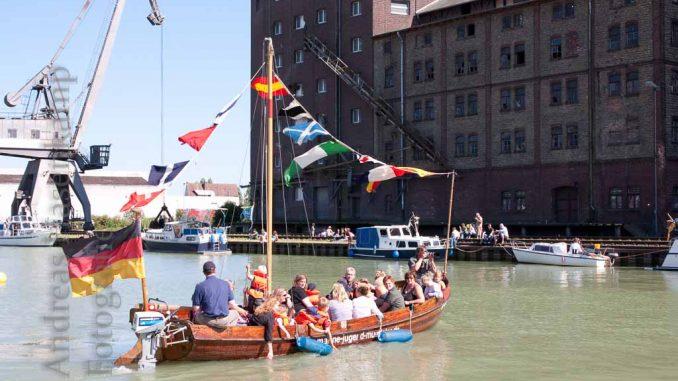 Gäste des Hafenfests in Münster 2009 auf einem motorgetriebenen Holzboot vor einem Kran. Foto: A. Hasenkamp, Fotograf in Münster.