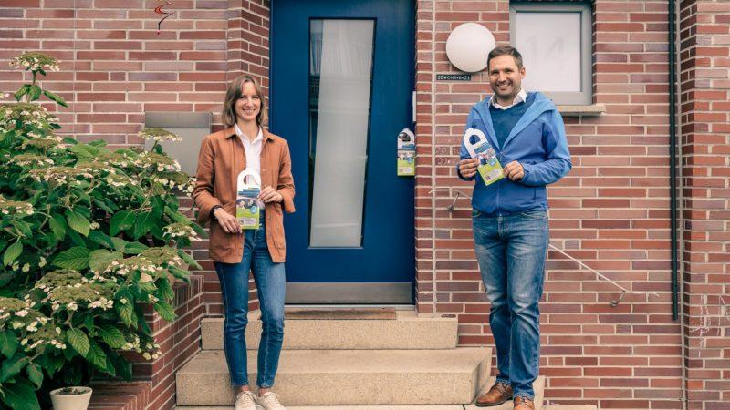 Ramona Leusch und Georg Reinhardt von der städtischen Koordinierungsstelle für Klima und Energie präsentieren die Türhänger der Photovoltaik-Kampagne. Foto: Amt für Kommunikation, Stadt Münster.