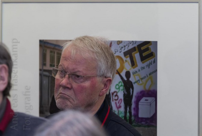 Winni Nachtwei vor einem Foto, auf dem drei Frauen vor einer Aufforderung zum Wählen vorbeigehen. Vernissage Geliebtes Afghanistan mit Professor Dr. Thomas Sternberg und Carl Wilhelm Macke von jhj. Foto: A. Hasenkamp, Fotograf in Münster.