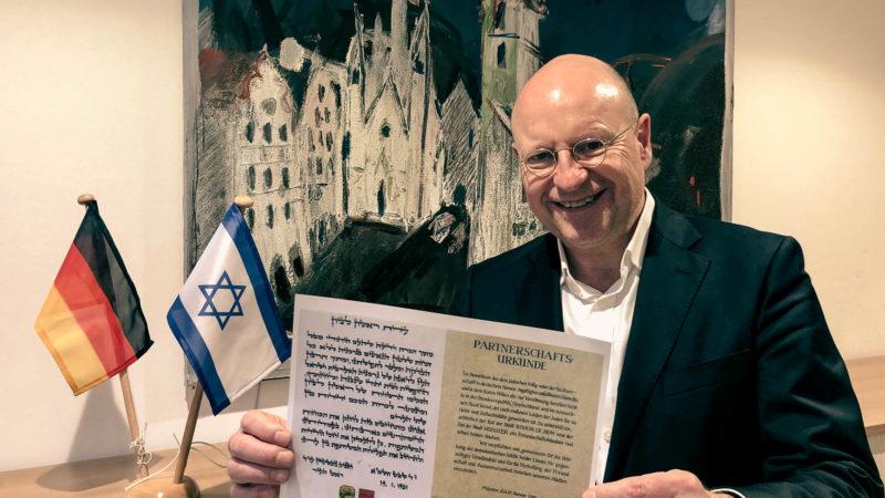 Oberbürgermeister Markus Lewe präsentiert die Urkunde, mit der die Partnerschaft zwischen Rishon LeZion und Münster vor genau 40 Jahren besiegelt wurde. Foto: Stadt Münster.