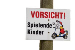 """Schild mit der Aufschrift: """"Vorsicht! Spielende Kinder!"""" Mit dem Bild eines Kindes auf einem Tretroller"""