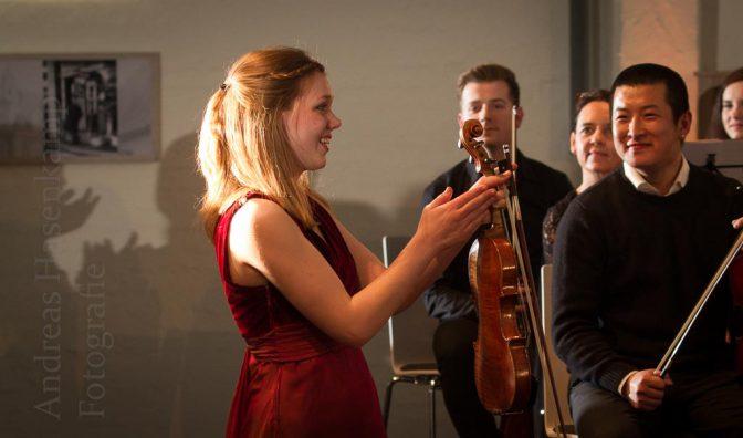 Judith Stapf applaudiert dem EinKlang-Orchester, dirigiert von Joachim Harder - das Publikum applaudiert (als Schatten) mit in der ehemaligen Maschinenhalle der Westfalen AG. Foto: A. Hasenkamp, Fotograf in Münster.