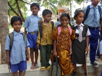 Kinder in Indien, teils mit Schulsachen.
