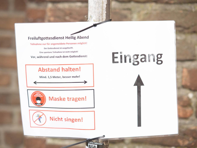 Heiligabend in Wolbeck zu Corona-Zeiten - Schilder am Eingang zum Wortgottesdienst im Hof des Drostenhofs. Foto: A. Hasenkamp.