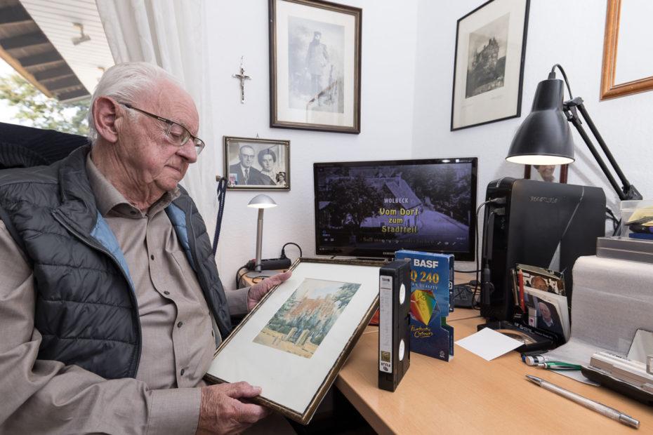 Heinrich Gallenkämper mit einem Bild seiner Eltern, einer von vielen Video-Kassetten, seinem neuesten Video auf dem PC-Monitor und einem Gemälde von 1935. Foto: A. Hasenkamp.