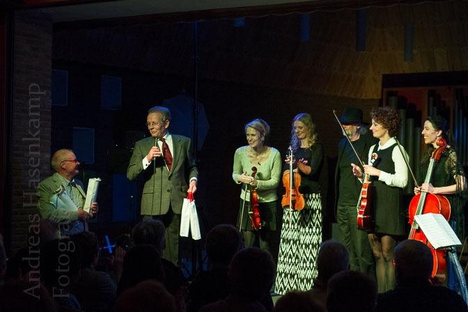 Karlheinz Kleintje und Raymund Droste zu Senden überreichen den Musikern ein flaschenförmiges Geschenk.