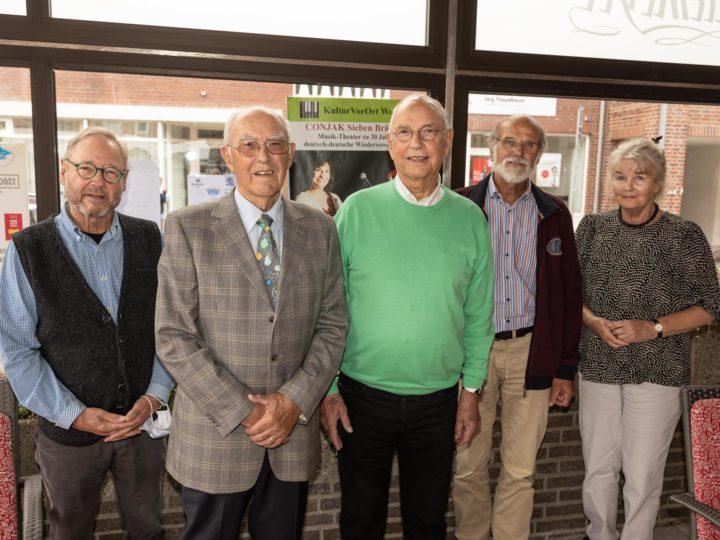 Hans Rath (2. v.l.) und Rolf Müller (3.v.l.), umgeben vom neuen Vorstand um Peter van Bevern (v.l.) mit Werner Rückamp und Gertrud Wohlthat (es fehlt Christoph Lammen) sowie im Hintergrund dem Plakat für das nächste Musik-Theater.