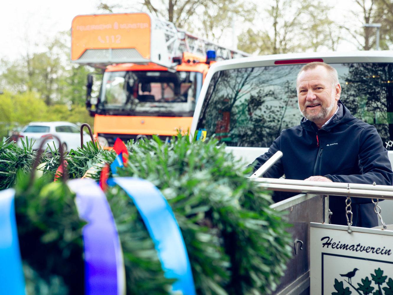 Andreas Schwegmann schafft den Kranz und die Scilder für den Maibaum heraan - für das Maibaum-Schmücken in Wolbeck.