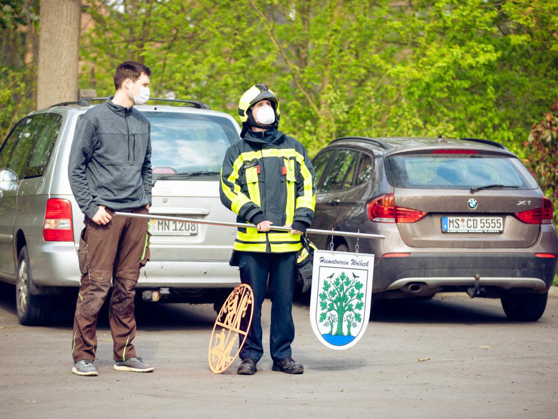 Sebastian Ringbeck hält Schildern von Feuerwehr und Heimatverein Wolbeck bereit für den Weg hoch in den Maibaum.
