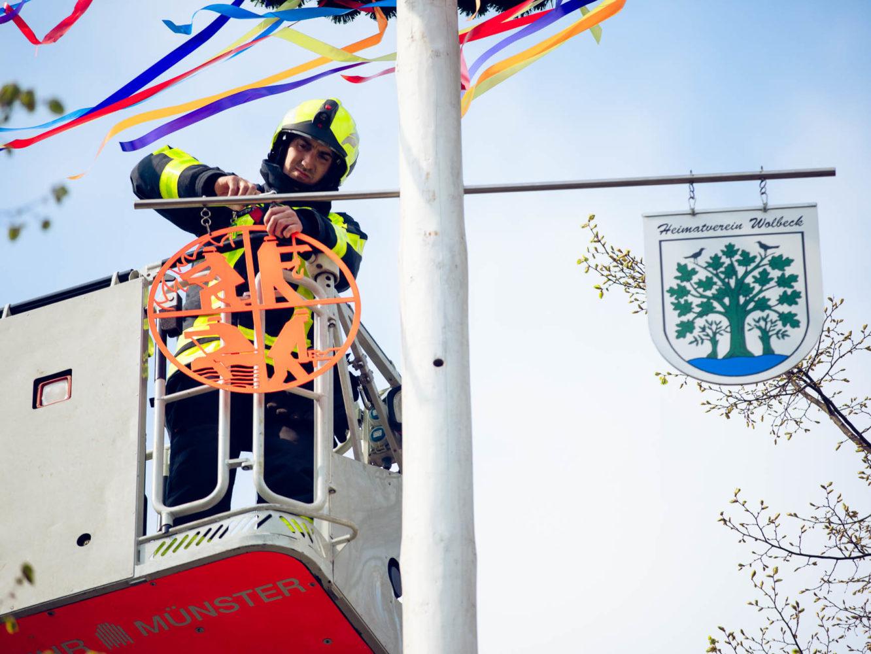 Christoph Dreyer befestigt das Schild der Feuerwehr am Maibau.m beim Maibaum-Schmücken in Wolbeck.