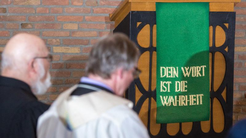 """""""Dein Wort ist die Wahrheit"""" steht auf dem Tuch vor dem Ambo in der Christuskirche, links sitzen nebeneinander Gerhard Trottier und Thomas Schulz. Foto: A. Hasenkamp."""