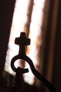 Kreuz am Weihwasser-Halter im Gegenlicht des Kirchenfensters