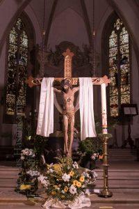 Blumenschmuck vor dem Kreuz mit Corpus Christi.
