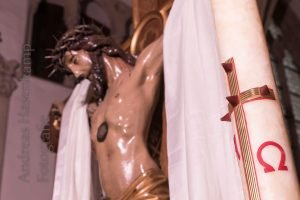Kreuz mit Corpus Christ ziwschen Tüchern hinter der Osterkerze