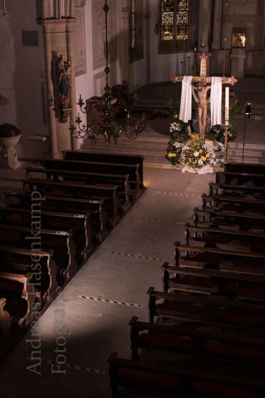 Blick von der Orgel-Empore auf den Gang mit Abstands-Streifen vor dem heruntergelassenen Kreuz