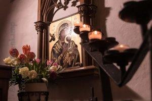 Hinter Kerzen: Ikone mit der Mutter Gottes.