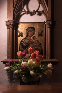 Bildnis der Mutter Gottes hinter Tulpen