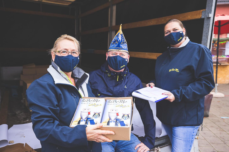 Andre Schlüter, Torsten Laumann und Ela Brüggemann. verteilen am Marktplatz weitere Kartons mit Sessionsheften. Foto: A. Hasenkamp.